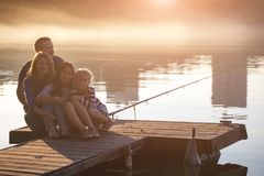 Happy family  sitting on the pier Royalty Free Stock Photography