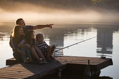 Happy family  sitting on the pier Stock Photography