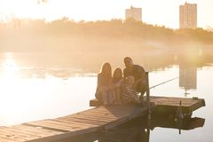 Happy family  sitting on the pier Stock Image