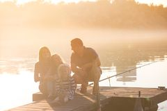 Happy family  sitting on the pier Stock Photo