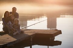 Happy family  sitting on the pier Royalty Free Stock Photos
