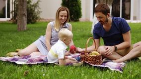 Happy family sitting on a plaid at the picnic on the green beautiful meadow on a sunny day. Their son is sitting near. Enjoy the picnic. Outdoors stock video footage