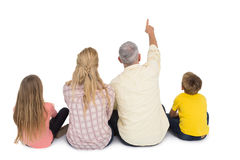 Happy family sitting and pointing Royalty Free Stock Photos