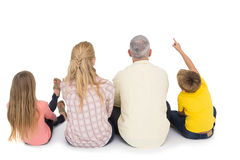 Happy family sitting and pointing Stock Photo