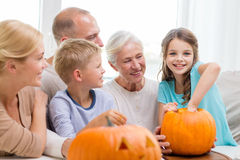 Happy family sitting with pumpkins at home Stock Image