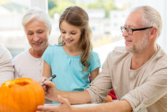 Happy family sitting with pumpkins at home Royalty Free Stock Photo
