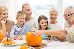 Happy family sitting with pumpkins at home Stock Images