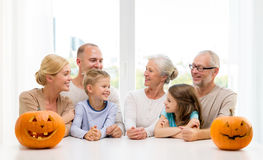 Happy family sitting with pumpkins at home Royalty Free Stock Photography