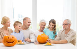 Happy family sitting with pumpkins at home Stock Photos