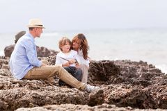 Happy family sitting on rock and watching ocean Royalty Free Stock Photo