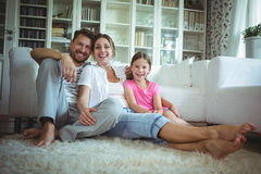 Happy family sitting on the rug in living room Stock Photography