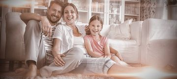 Happy family sitting on rug in living room stock photography