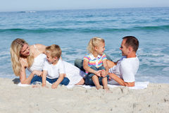 Happy family sitting on the sand Royalty Free Stock Images