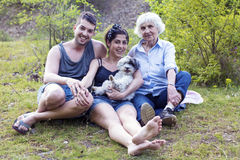 Happy family sitting and smiling in the park Royalty Free Stock Photos