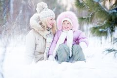Happy family sitting in snow outdoor wintertime Stock Image