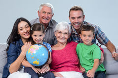 Happy family sitting on sofa. Cheerful family sitting on sofa with a globe in living room Stock Images