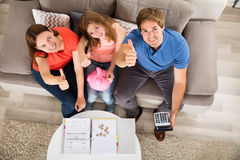 Happy Family Sitting On Sofa Gesturing Thumbs Up stock photos