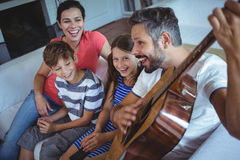 Happy family sitting on sofa with a guitar. Portrait of happy family sitting on sofa with a guitar stock image