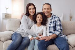 Happy family sitting on the sofa. Happy family. Pretty joyful curly-haired girl smiling and sitting on the couch with her parents and they hugging her Stock Images