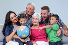 Happy family sitting on sofa. Holding a globe in living room Royalty Free Stock Photo