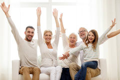 Happy family sitting on sofa at home. Family, happiness, generation and people concept - happy family sitting on sofa and rising hands at home Royalty Free Stock Photo