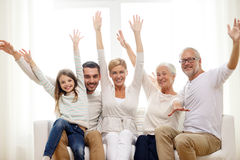 Happy family sitting on sofa at home. Family, happiness, generation and people concept - happy family sitting on sofa and rising hands at home Stock Images