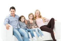 Happy family sitting on the sofa at home isolated. Royalty Free Stock Photography