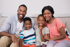 Happy family sitting on sofa at home. Portrait of happy family sitting on sofa at home royalty free stock photo