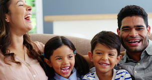 Happy family sitting on sofa and laughing in living room stock video footage