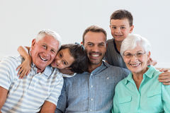 Happy family sitting on sofa. Portrait of happy family sitting on sofa and smiling in living room Stock Photos