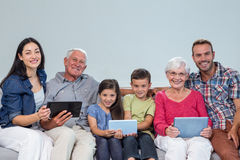 Happy family sitting on sofa. Portrait of happy family sitting on sofa using a digital tablet in living room Royalty Free Stock Photo
