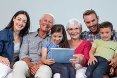 Happy family sitting on sofa. Portrait of happy family sitting on sofa using a digital tablet in living room Royalty Free Stock Image