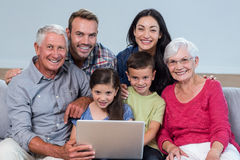 Happy family sitting on sofa. Portrait of happy family sitting on sofa using a laptop in living room Stock Photo