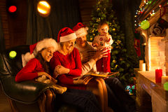 Happy family sitting on sofa while reading a story book in Christmas decorated room. At home Royalty Free Stock Image