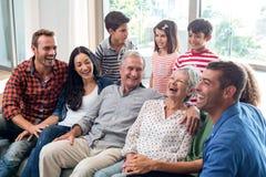 Happy family sitting on sofa royalty free stock photos