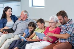 Happy family sitting on sofa. Using a digital tablet in living room Stock Image