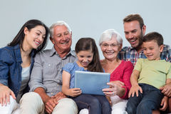 Happy family sitting on sofa. Using a digital tablet in living room Royalty Free Stock Photography