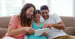 Happy family sitting on sofa and using digital tablet stock video footage