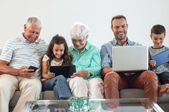 Happy family sitting on sofa. Using a laptop, digital, tablet, mobile phone in living room Stock Photography