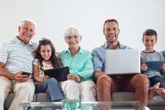 Happy family sitting on sofa. Using a laptop, digital, tablet, mobile phone in living room Royalty Free Stock Photography