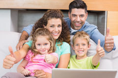 Happy family sitting on sofa using laptop giving thumbs up Stock Photo
