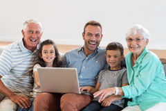 Happy family sitting on sofa. Using a laptop in living room Royalty Free Stock Image