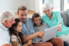 Happy family sitting on sofa. Using a laptop in living room Stock Photography