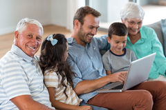 Happy family sitting on sofa. Using a laptop in living room Royalty Free Stock Images
