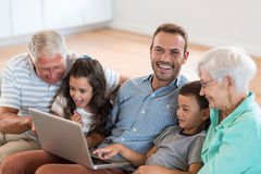 Happy family sitting on sofa. Using a laptop in living room Royalty Free Stock Photo