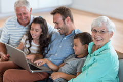 Happy family sitting on sofa. Using a laptop in living room Stock Photos