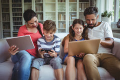 Happy family sitting on sofa and using laptop, mobile phone and digital tablet Stock Photos