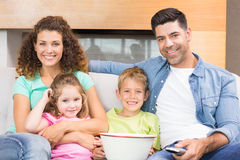 Happy family sitting on sofa watching tv with popcorn Stock Photography