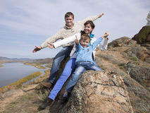 Happy family sitting on the stone and showing thumb Royalty Free Stock Image
