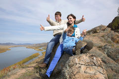 Happy family sitting on the stone and showing thumb Royalty Free Stock Photos
